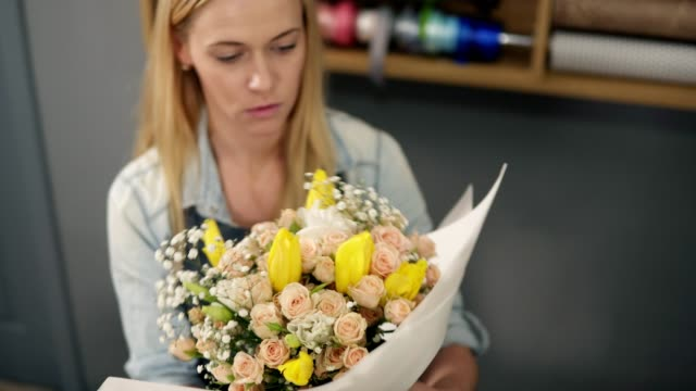 Young blonde female florist wrapping a bunch of flowers in decorating paper video