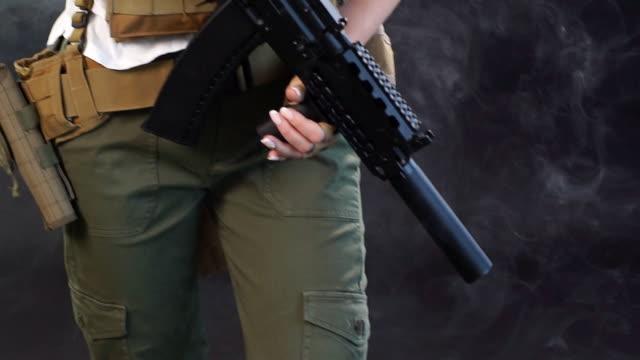 若いブロンドの女性は、スタジオでアサルトライフルで軍事服を着て断片 - 美人点の映像素材/bロール