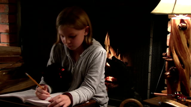 Young blonde girl does homework by fireplace video