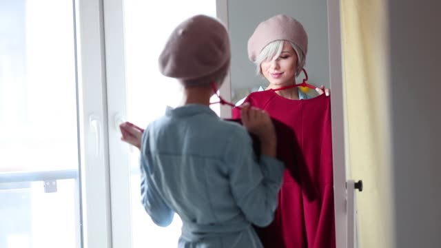 Young blonde girl dressing up at home Young blonde girl in beret dressing up at home near a mirror. dress stock videos & royalty-free footage