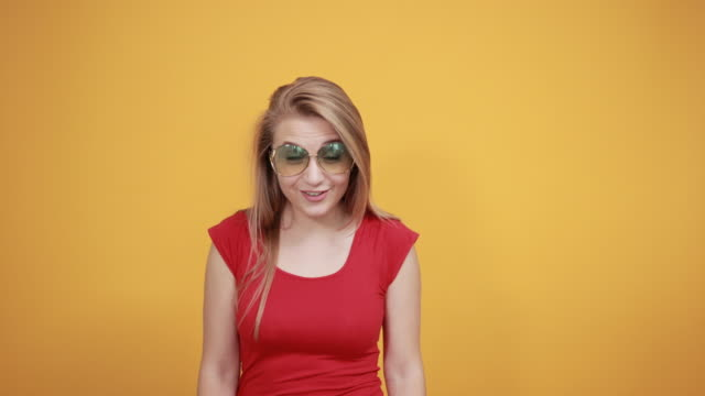 young blonde girl in red t-shirt over isolated orange background shows emotions