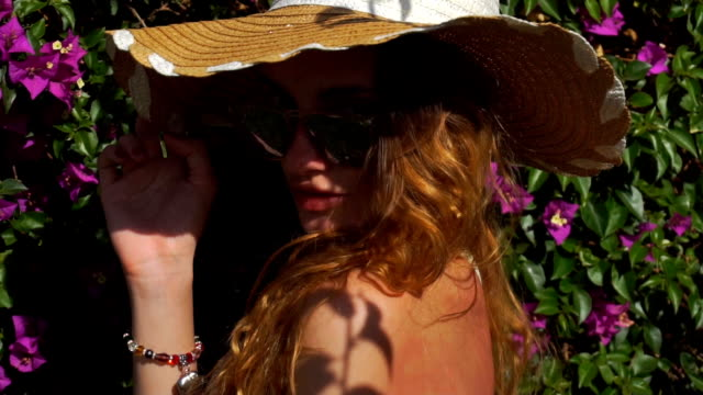 young blonde girl in sunglasses and straw hat posing in the blooming garden video