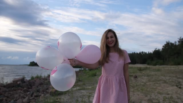 vídeos de stock e filmes b-roll de a young blonde in a pink dress is walking along the beach with balls. then she releases the balls into the camera. 4k slow mo - mulher balões