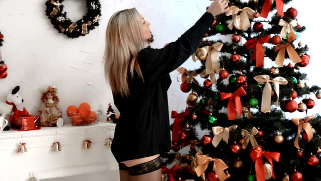 young blonde in black shirt and stockings hang on the christmas tree toys and smiling - top nero video stock e b–roll