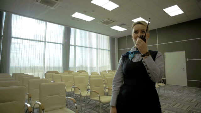 Young blonde in the conference hall of the airport makes an ad video