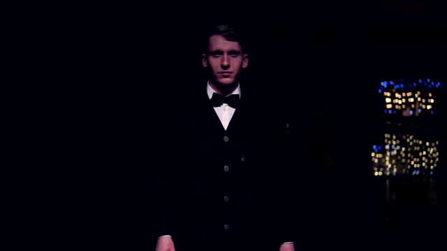 Young blonde man in a black suit with bow-tie coming out from dark to light and smiling. Slowmotion video