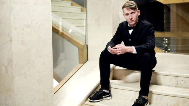 Young blonde man in black suit using his smartphone and sitting on stairs in hotel. Waiting for someone video