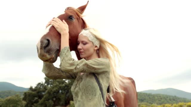 Jeune blonde femme souriante dans la nature en plein air SWING et hug portrait de brun Cheval-séquences vidéo HD - Vidéo