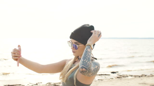 young blonde with a tattoo in sunglasses and a choker takes off on the phone on the seashore close-up - tatuaggio video stock e b–roll