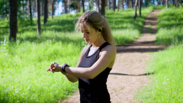 A young blonde woman changes settings on a smart watch, an athlete who runs runs wants to know how many kilometers she ran video