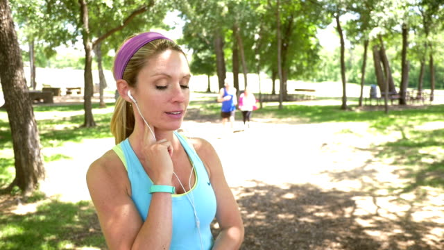 Young blonde woman checks pulse before running on trail video