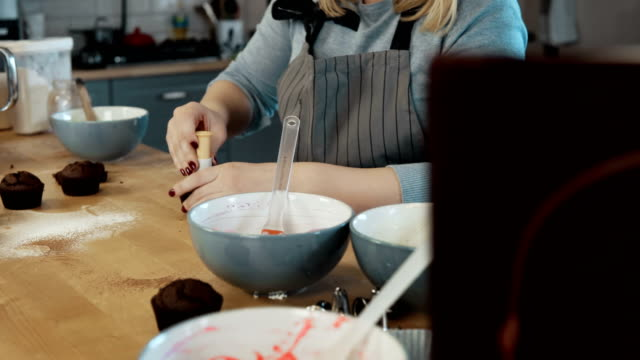Young blonde woman cooking the cupcakes on the kitchen. Beautiful female using the cutter to making muffins video
