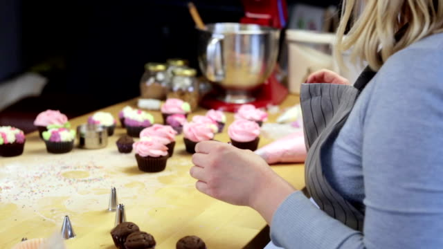 Young blonde woman decorating cupcakes with colored cream. Beautiful confectioner using the pastry bag for cooking video