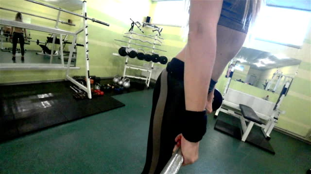 Young blonde woman doing exercises with barbbell in a GYM. video