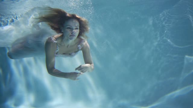 young blonde woman in vintage white dress swimming underwater - capelli biondi video stock e b–roll