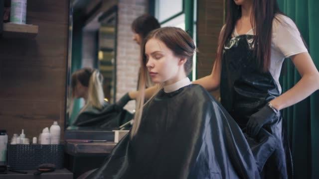 vidéos et rushes de jeune femme blonde est assis sur chaise dans un salon de beauté, tandis que le salon de coiffure est de redresser une cape et délie ses longs cheveux - salons et coiffeurs