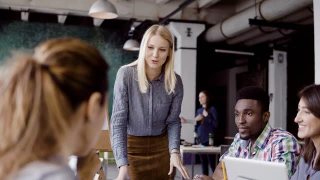 젊은 금발 여자 매니저 혼합된 경주 팀과 함께 얘기. 현대 사무실에서 동료에 게 방향을 주는 사업가 - modern office 스톡 비디오 및 b-롤 화면