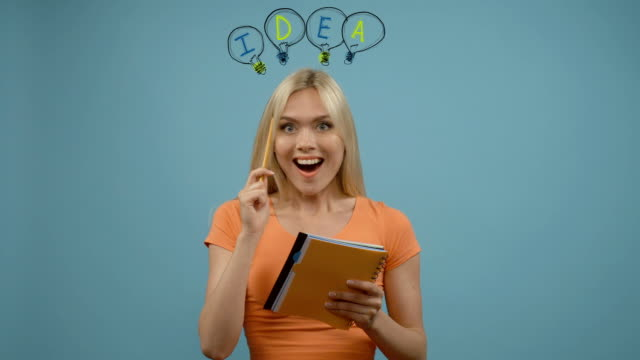 Young blonde woman standing in front of blue wall looking away with notepad, searching for solution of problem, bulbs hovering from above video