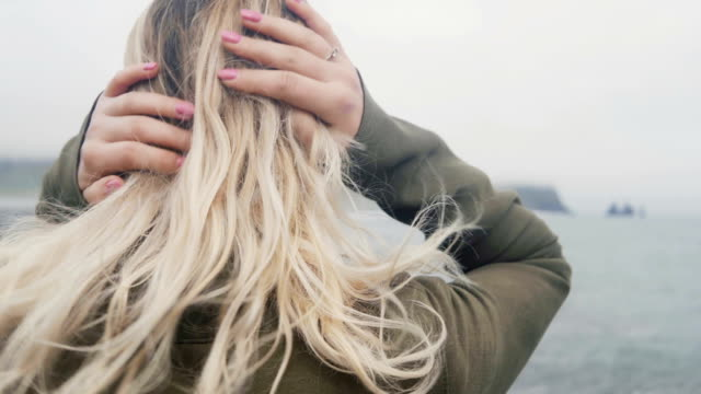 Young blonde woman standing on the beach, near the troll toes in Iceland, doing up hair and looking on the water video