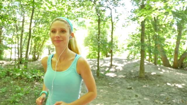 молодая белокурая женщина, используя наушники во время пробежки на пути грязи - аксессуар для волос стоковые видео и кадры b-roll
