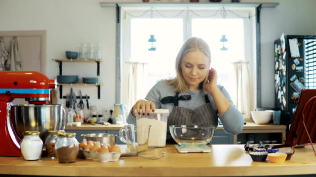 Young blonde woman using the kitchen scales to weighing the flour. Beautiful female baking the cupcakes on the kitchen video