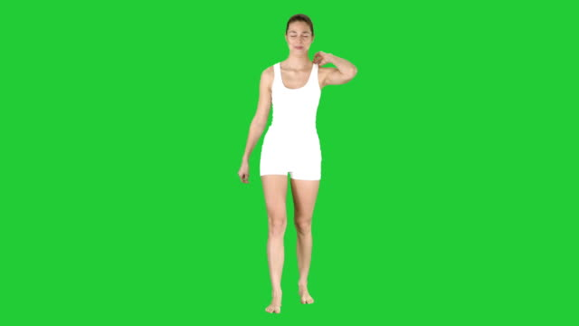 vídeos de stock e filmes b-roll de young blonde woman with happy face smiling doing ok sign on a green screen, chroma key - soccer supporter portrait