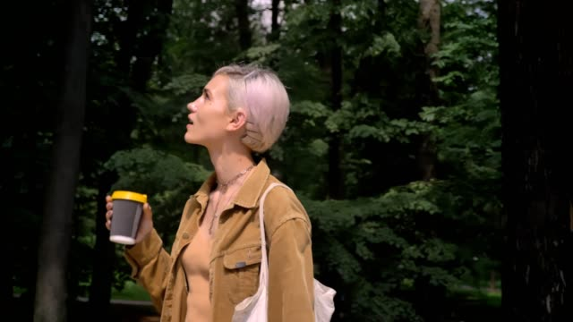 young blonde woman with short hair drinking coffee and going from park to her car - woman portrait forest video stock e b–roll