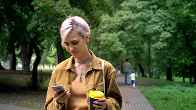 young blonde woman with short haircut walking in park and typing on phone, holding coffee - природный парк стоковые видео и кадры b-roll