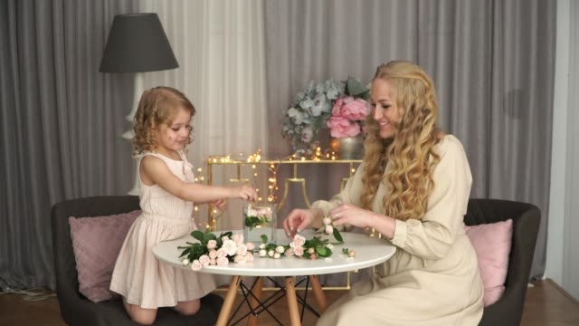 Young blondes beautiful mother and cute 5 year old daughter sit at table and make bouquet of pink roses.
