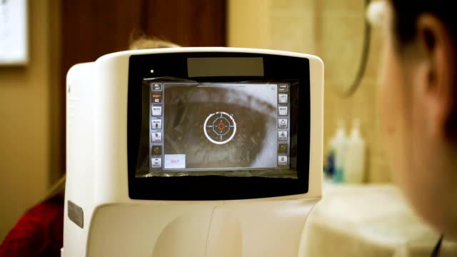 vidéos et rushes de jeune femme blonde-cheveux examinant sa vue à l'optométriste. hd - examen ophtalmologique