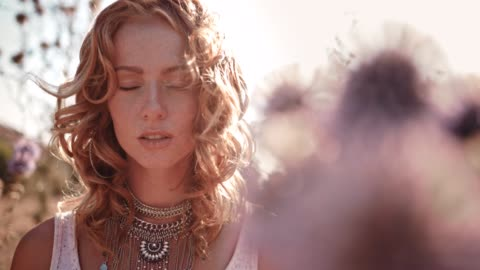 Young boho woman with freckles standing in wildflowers field Young hippie woman in boho style and silver jewelry standing among wildflowers in autumn field boho stock videos & royalty-free footage
