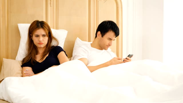 Young bored couple using their mobile phone in bed Young bored couple using their mobile phone in bed ignoring stock videos & royalty-free footage