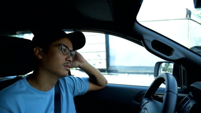 young boring asian man driving a car on traffic jam. - ingorgo stradale video stock e b–roll
