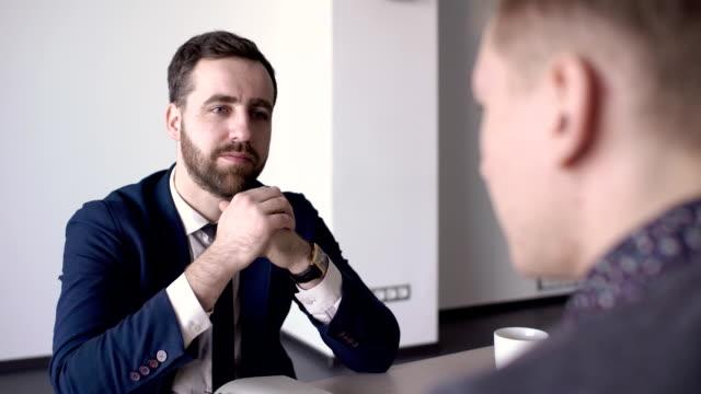 junger chef kommuniziert mit männlichen mitarbeiter in modernen büro - unterordnung stock-videos und b-roll-filmmaterial