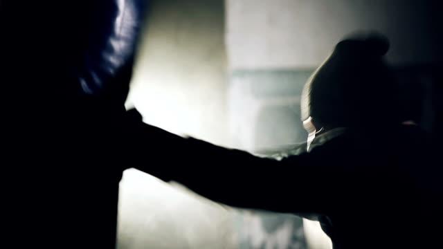 Joven boxeador combate sobre fondo negro en el club de deportes del metro - vídeo