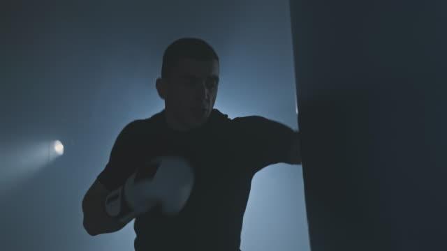 young boxer training in low light gym. sportsman boxing in smoky studio. 4k, uhd - sacco per il pugilato video stock e b–roll