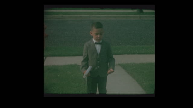 1964 young boy all dressed up in suit and bow tie - костюм в комплекте стоковые видео и кадры b-roll