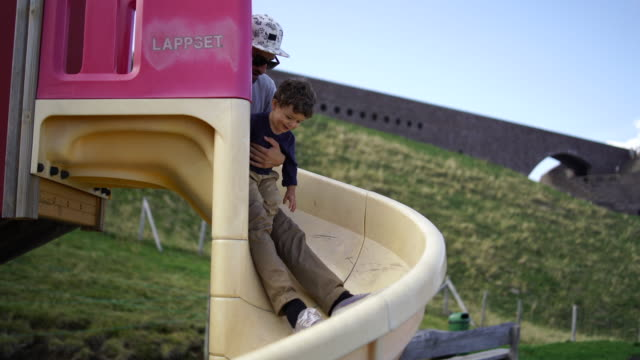 young boy  and father ride down slide - scivolo video stock e b–roll