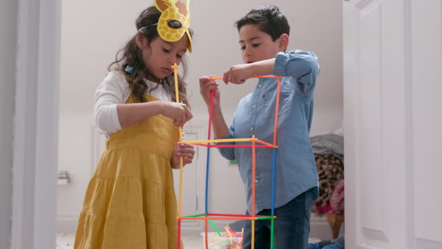 A young boy and girl building a construction toy together