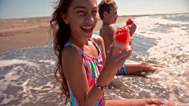 Young boy and girl eating watermelon on the beach