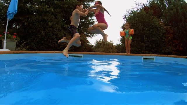 Young boy and girl jump into a swimming pool holding hands video