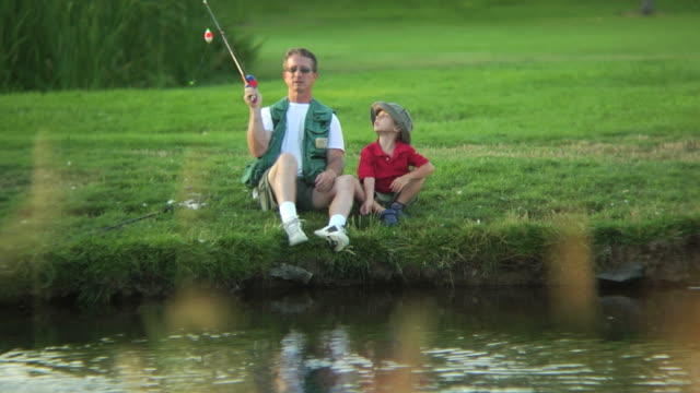 Young boy and grandfather fishing video
