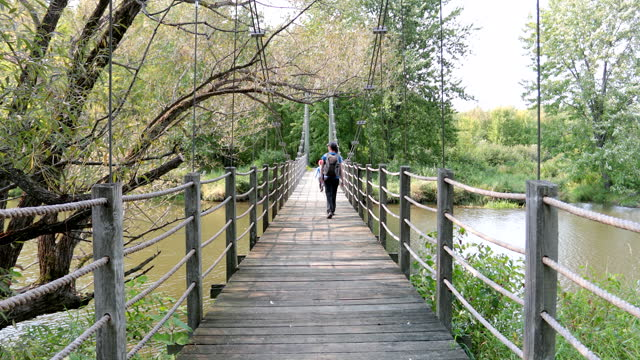 Young Boy and His Mother Running on Suspension Bridge in Summer