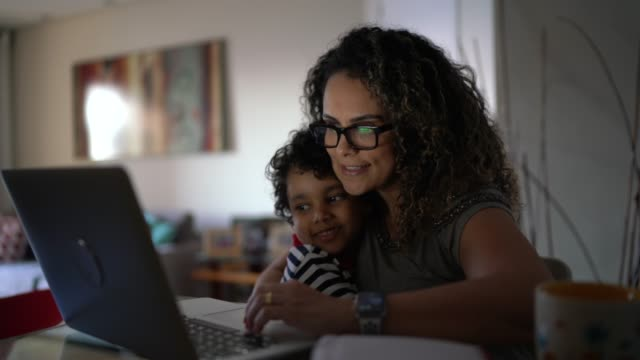 Young boy arriving to embrace mother while she is working at home
