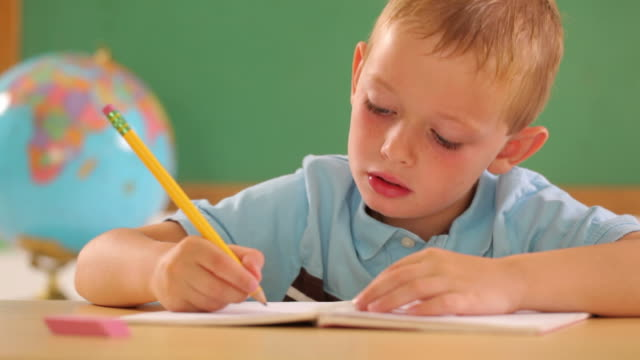 stockvideo's en b-roll-footage met young boy at school writing with pencil - bureauglobe
