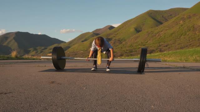 vídeos de stock e filmes b-roll de young boy businessman lifting weights - antecipação