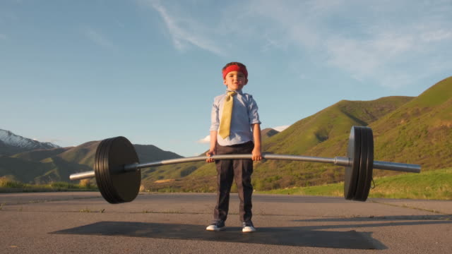 young boy businessman lifting weights - fare la lotta video stock e b–roll