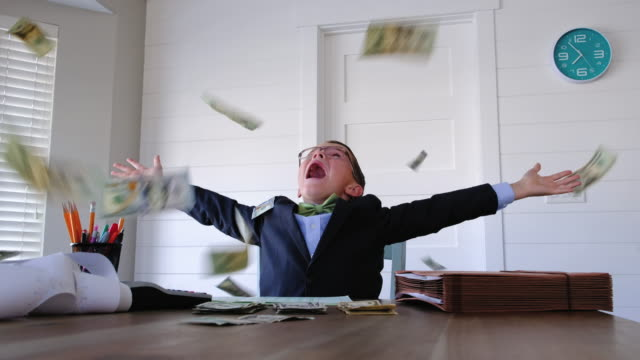 Young Boy Businessman Throwing Money A young entrepreneur boy businessman is dressed in business attire and is working hard on his business while earnings in US currency and cash are raining from the sky. He loves earning money from his new business and saving his money in the bank. 4K resolution video. wealth stock videos & royalty-free footage
