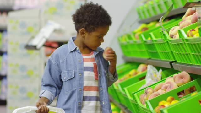 young boy buying peaches at supermarket - pesche bambino video stock e b–roll