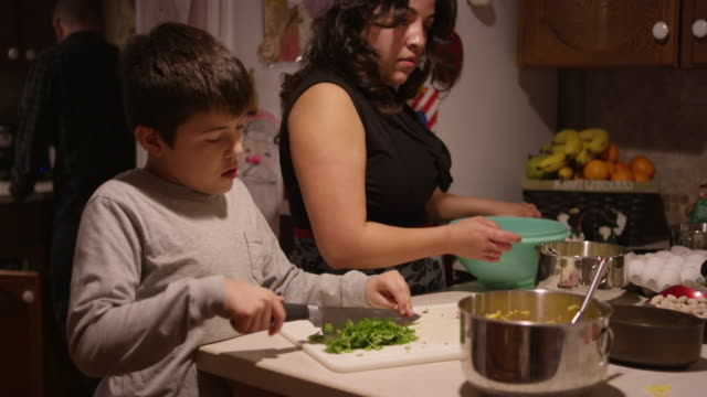 A young boy chopping vegetables in the kitchen with his mother video